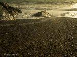 ocean foam creeps between the stones